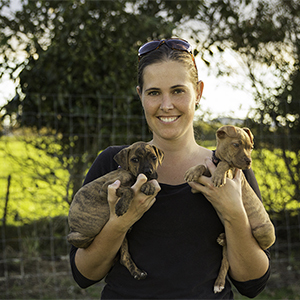 DC Rescue Dogs Founder Cherie with two small puppies